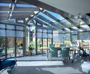 Immagine d'assieme di tende a rullo e frangisole mobili installati su pareti e soffitti vetrati a protezione solare